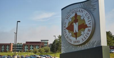 A sign with NMU's seal in the foreground. Jamrich Hall is in the background.